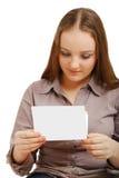 Adolescente que lee una tarjeta. Imagen de archivo libre de regalías