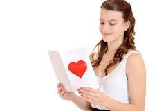 Adolescente que lee una tarjeta de las tarjetas del día de San Valentín Foto de archivo
