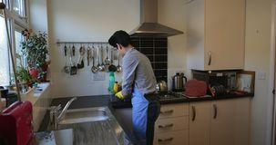 Adolescente que limpa a cozinha video estoque