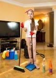 Adolescente que limpia el piso de madera con el cepillo y la cucharada Foto de archivo libre de regalías