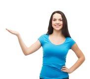 Adolescente que lleva a cabo algo en la palma de su mano Imágenes de archivo libres de regalías
