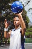 Adolescente que lleva a cabo baloncesto mientras que practica ante el tribunal Imagen de archivo