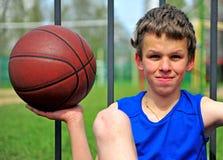 Adolescente que lleva a cabo el baloncesto Imágenes de archivo libres de regalías