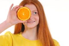 Adolescente que lleva a cabo el pedazo de naranja delante de su ojo Imagenes de archivo