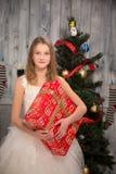 Adolescente que lleva a cabo el regalo de Navidad delante del árbol del Año Nuevo Imágenes de archivo libres de regalías