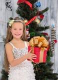 Adolescente que lleva a cabo el regalo de Navidad delante del árbol del Año Nuevo Fotografía de archivo