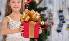 Adolescente que lleva a cabo el regalo de Navidad delante del árbol del Año Nuevo Foto de archivo libre de regalías