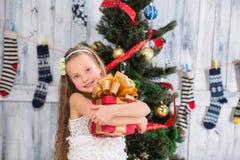Adolescente que lleva a cabo el regalo de Navidad delante del árbol del Año Nuevo Fotos de archivo