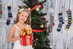 Adolescente que lleva a cabo el regalo de Navidad delante del árbol del Año Nuevo Imagenes de archivo