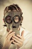 Adolescente que lleva a cabo la careta antigás en cara Foto de archivo libre de regalías