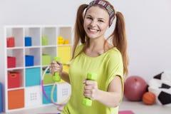 Adolescente que lleva a cabo pesas de gimnasia Foto de archivo