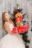 Adolescente que lleva a cabo regalos de Navidad delante del árbol del Año Nuevo Imagen de archivo
