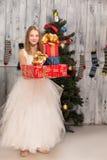 Adolescente que lleva a cabo regalos de Navidad delante del árbol del Año Nuevo Fotos de archivo