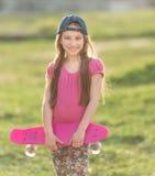 Adolescente que lleva a cabo a su tablero rosado Imagen de archivo libre de regalías