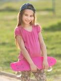Adolescente que lleva a cabo a su tablero rosado Foto de archivo