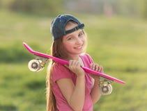 Adolescente que lleva a cabo a su tablero rosado Fotos de archivo