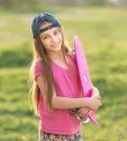 Adolescente que lleva a cabo a su tablero rosado Imagen de archivo