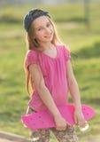 Adolescente que lleva a cabo a su tablero rosado Imagenes de archivo