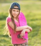 Adolescente que lleva a cabo a su tablero rosado Fotografía de archivo libre de regalías