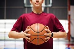 Adolescente que lleva a cabo un baloncesto en la corte Foto de archivo libre de regalías