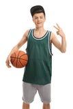 Adolescente que lleva a cabo un baloncesto y que hace un gesto de la victoria Fotos de archivo libres de regalías