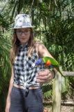 Adolescente que lleva a cabo un lorikeet colorido del arco iris Fotografía de archivo libre de regalías