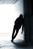 Adolescente que lleva a cabo una botella y una situación de cerveza en el callejón Imagen de archivo