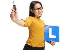 Adolescente que lleva a cabo una llave del coche y una L-muestra Fotografía de archivo