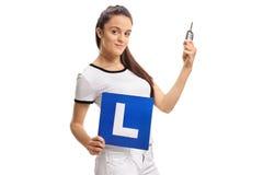 Adolescente que lleva a cabo una llave del coche y una L-muestra Imagen de archivo libre de regalías