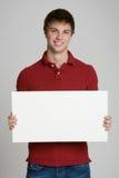 Adolescente que lleva a cabo una muestra en blanco aislada en blanco Imagen de archivo
