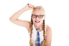 Adolescente que lleva un uniforme escolar y los vidrios. Muchacha que rasguña su cabeza con una pluma. Fotografía de archivo libre de regalías