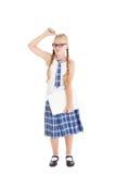 Adolescente que lleva un uniforme escolar y los vidrios que sostienen un ordenador portátil. Muchacha que rasguña su cabeza con un Imagen de archivo libre de regalías