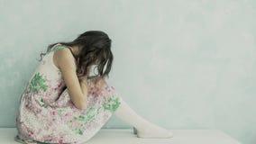 Adolescente que llora en casa cubriendo su cara con las manos Foto de archivo
