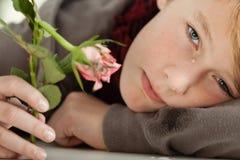 Adolescente que llora y que detiene a Rose rosada rota Fotos de archivo