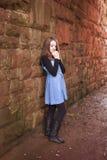 Adolescente que lo inclina contra una pared vieja con sus manos debajo Fotografía de archivo libre de regalías