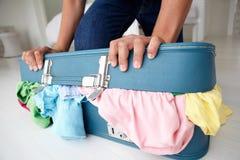 Adolescente que lucha para cerrar la maleta Foto de archivo libre de regalías