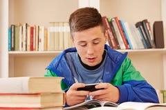 Adolescente que manda un SMS con smartphone mientras que estudia Fotografía de archivo