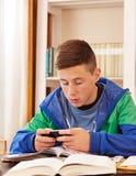 Adolescente que manda un SMS con smartphone mientras que estudia Fotografía de archivo libre de regalías