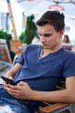 Adolescente que manda un SMS de su teléfono móvil Fotografía de archivo