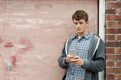 Adolescente que manda un SMS en el teléfono móvil en el ambiente urbano Imágenes de archivo libres de regalías