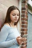 Adolescente que manda un SMS en el teléfono móvil en el ambiente urbano Fotografía de archivo libre de regalías