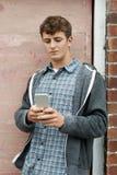 Adolescente que manda un SMS en el teléfono móvil en el ambiente urbano Fotografía de archivo