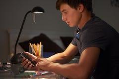 Adolescente que manda un SMS en el teléfono mientras que estudia en el escritorio en dormitorio por la tarde Foto de archivo