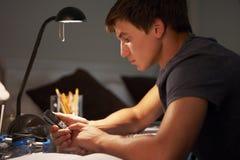 Adolescente que manda un SMS en el teléfono mientras que estudia en el escritorio en dormitorio por la tarde Imagen de archivo