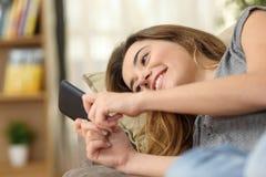 Adolescente que manda un SMS en un teléfono elegante en casa Fotografía de archivo