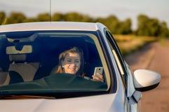 Adolescente que manda un SMS mientras que conduce el coche blanco Foto de archivo libre de regalías