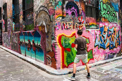 Adolescente que marca la pared de la pintada con etiqueta Fotografía de archivo