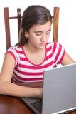 Adolescente que mecanografía en su ordenador portátil aislado en blanco Fotos de archivo libres de regalías