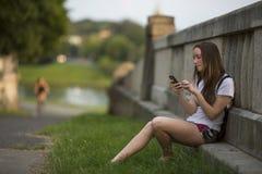 Adolescente que mecanografía un mensaje en smartphone, al aire libre El caminar Imagen de archivo