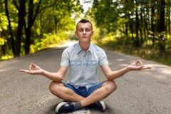 Adolescente que medita en el medio de un camino vacío Imágenes de archivo libres de regalías